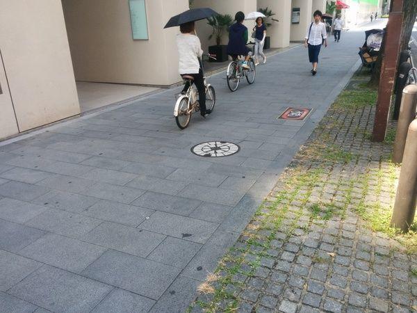 Gente andando en bicicleta sobre señal de no andar en bicicleta en Japón