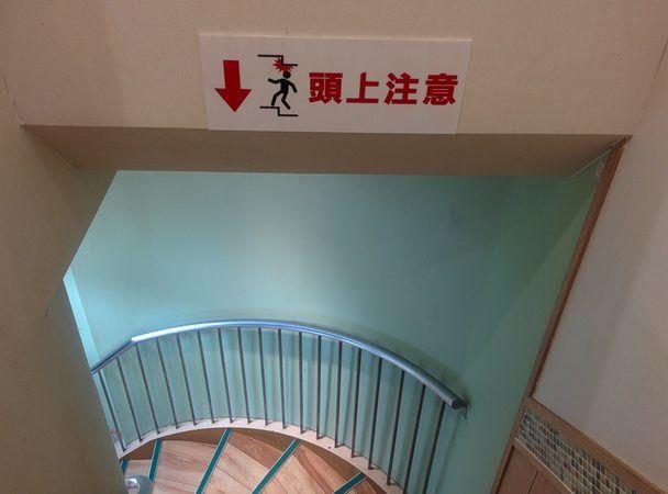 Señal indicando peligro de golpearnos la cabeza al bajar la escalera